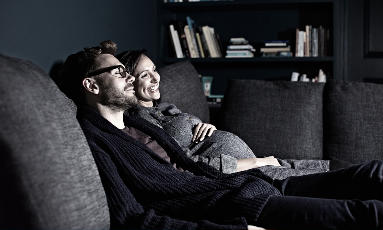 Husband and expectant wife watching TV in living room