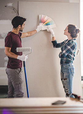 Young couple picking paint colors for living room
